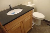 brand new bathroom sink with marble black countertop and wooden simple closet next to toilet seat