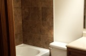 Modern bathroom interior with new white bathtub and toilet seat with brown tiles