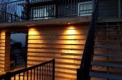 Warm highlights for outdoor patio space illuminating the wooden wall along the staircase
