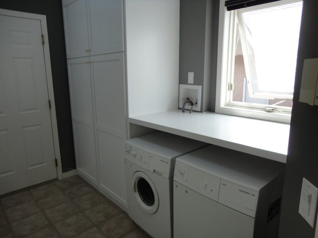Modern laundry room and basement interior renovating with big wide closets next to opened window and washers and dryer side by side