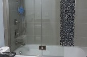 Modern bathroom renovated with shower hose and white bathtub with the pattern tiles along with grey tiles