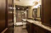 Modern bathroom interior in marble countertop and shower booth surrounded by brown colour closets and door