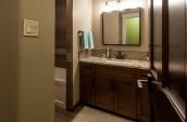 Modern Bathroom interior in dark brown closet and door and marble countertop with blue towels on the hanger