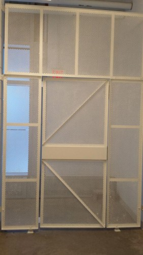 White meshed security gates installation with the door in front of exit sign