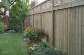 Wooden fence with the check pattern on the top placing next to little garden with flower and plants
