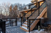 Modern Patio Interior with staircase in wooden covered in snow black stairway hand rail next to chopped firewoods