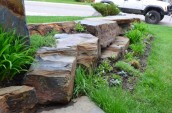 Beautiful brown stoneworks placed on the front yard area with small plants