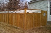 Wooden fence with the check pattern on the top placing just outside of house