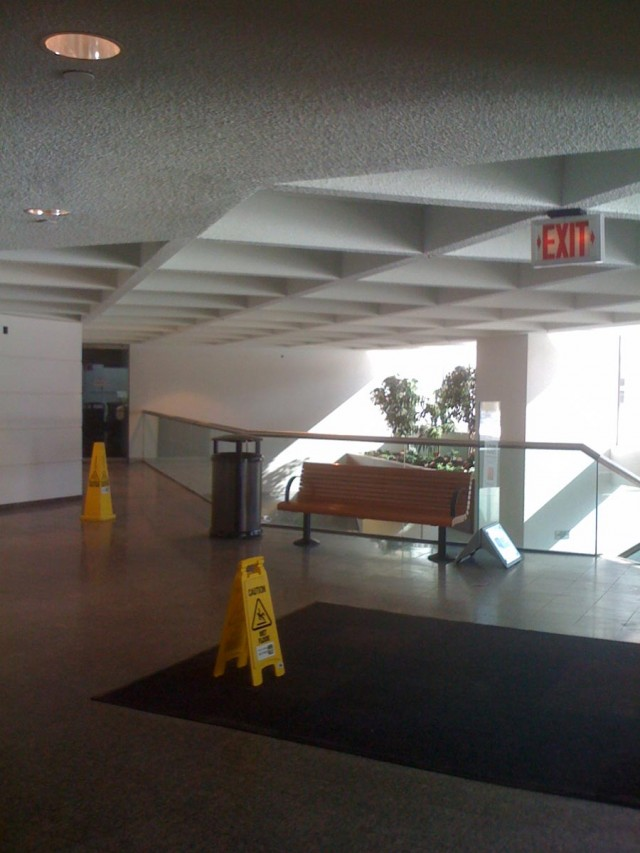 Modern commercial space with the bench and trash cans and yellow caution signs placing on the floor carpet