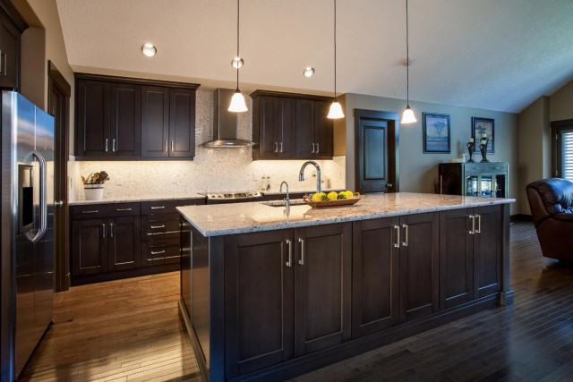 Modern Kitchen Interior in black closets and kitchen island with marble countertop