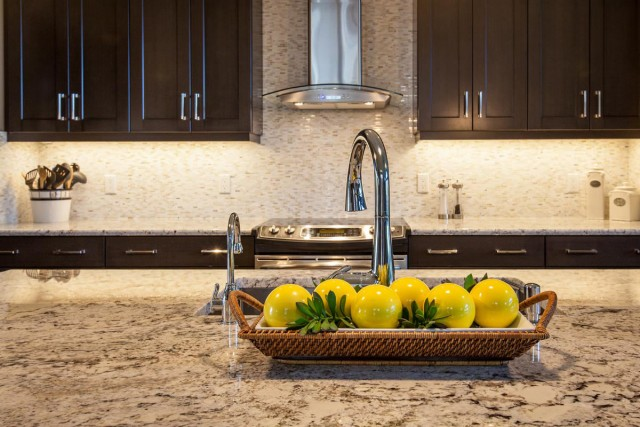 Modern Kitchen Interior in black closets and kitchen island with marble countertop and yellow round fruit ornaments
