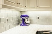 Modern Kitchen Interior deep purple blender is sitting on the marble countertop and light grey tiles on the wall and white closet