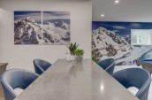 a long table with four seats in a newly renovated basement with pictures of mountains on the wall behind