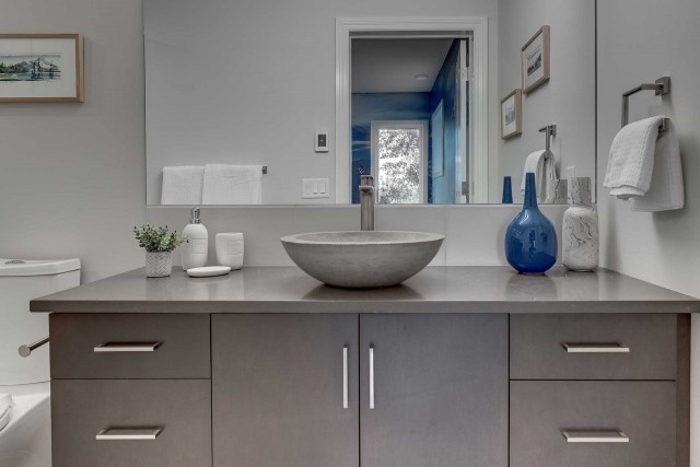 marble bowl shaped basin with empty vases to the right and large rectangular mirror above