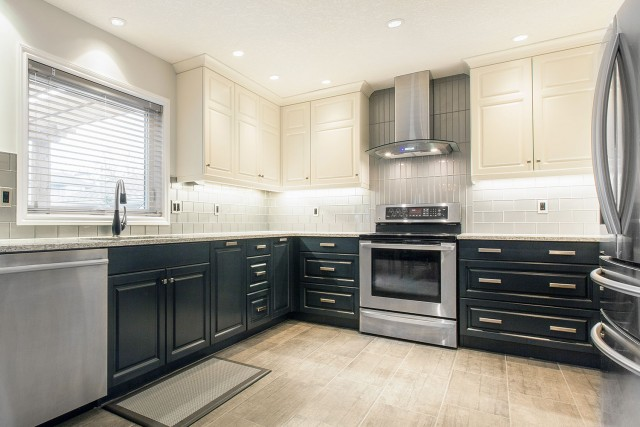 oven surrounded by drawers with extractor surrounded by cabinets