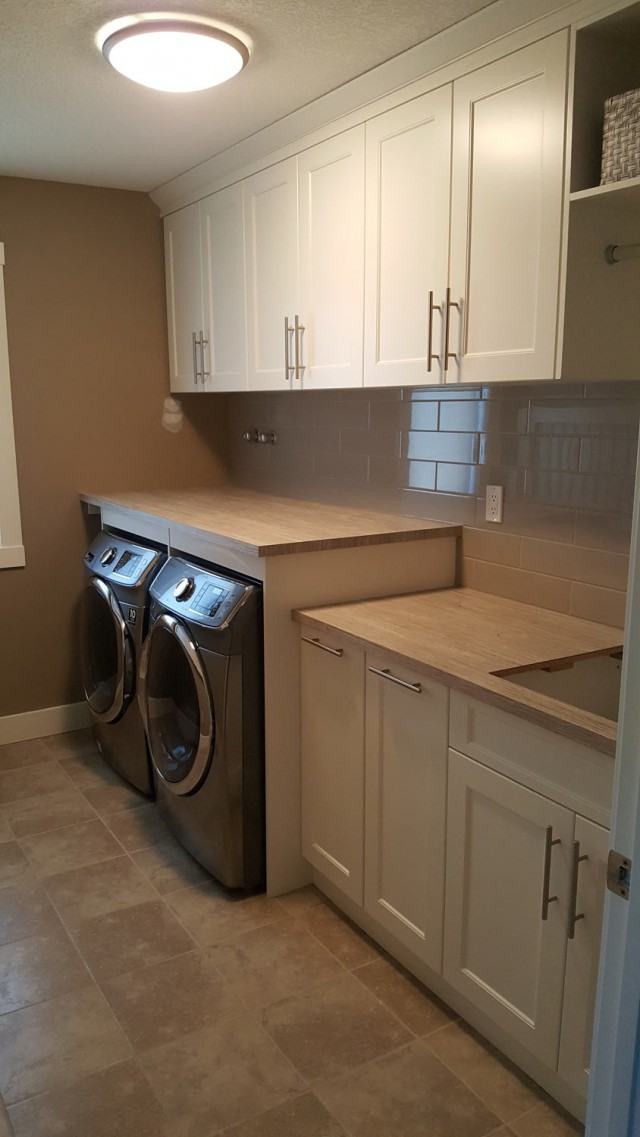 modern renovated laundry room with washer dryer and white shelving units on the floor and wall