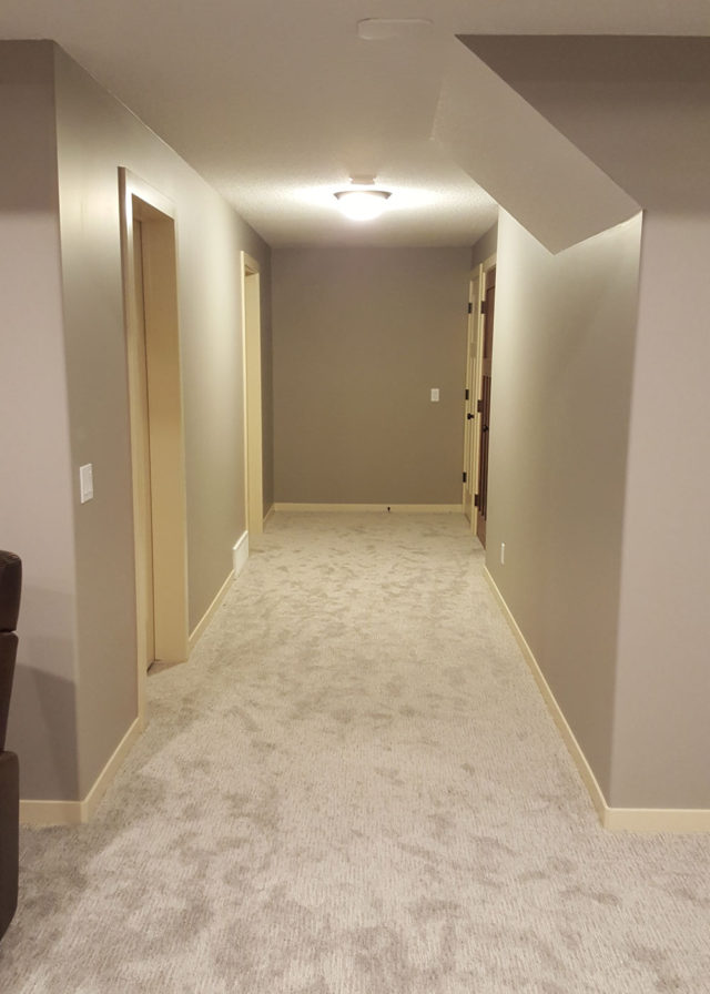 carpeted hallway with two doors to left and one to right