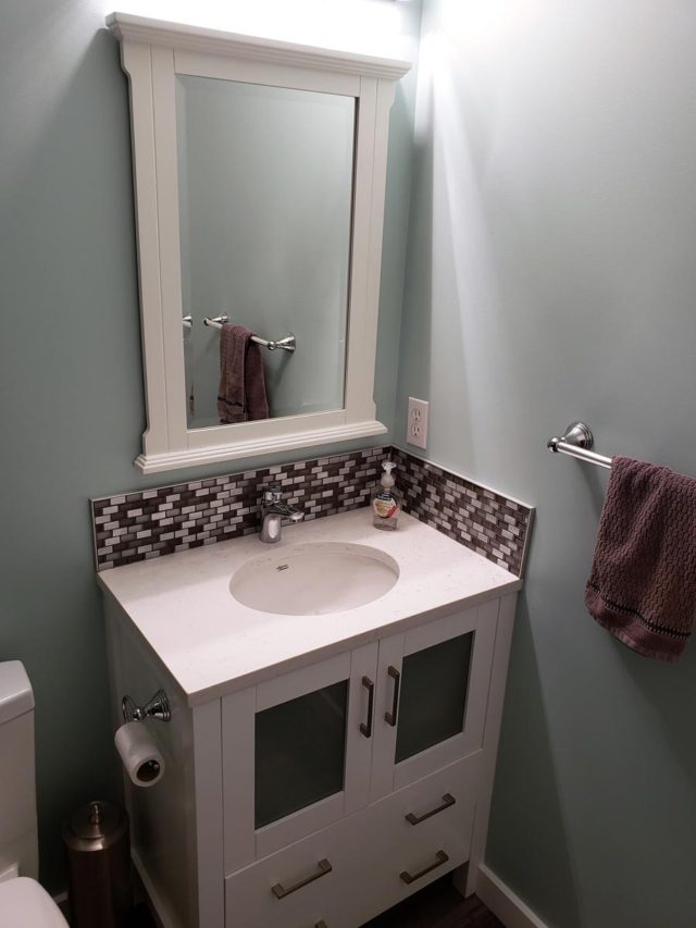 basin and mirror with towel hanging on towel rack