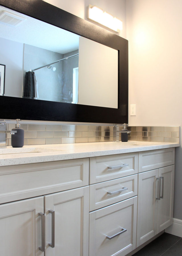 large rectangular mirror above drawers and cabinets in bathroom