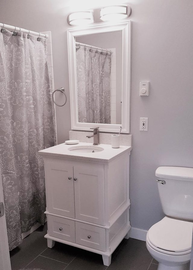 bathroom with closed shower curtain to the left, basin/mirror in the centre and toilet to the right