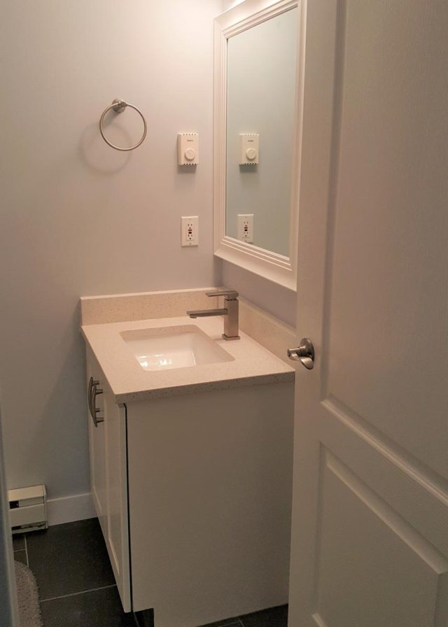 basin in corner of bathroom with towel ring on wall to the left
