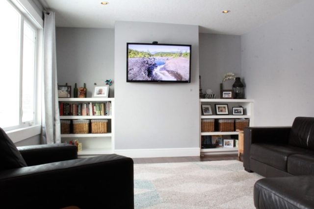 flat screen tv on wall with recessed bookshelves on either side and black leather furniture arranged for viewing