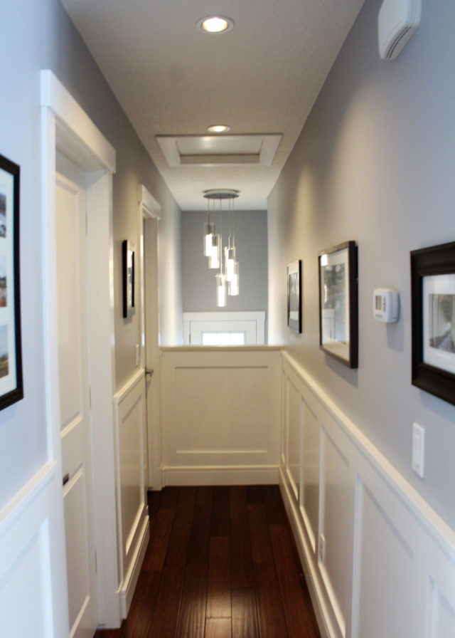 hallway with wooden floor and framed images hanging on wall