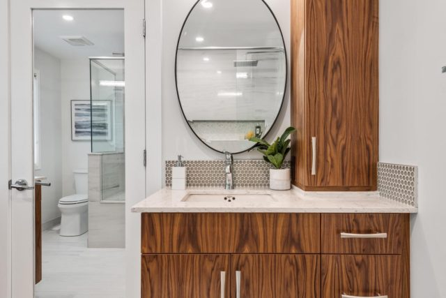 bathroom with wood veneer cabinet and round mirror above basin