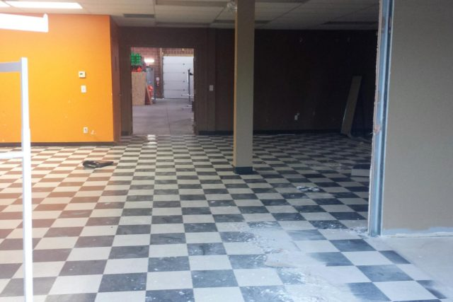 large room in commercial building with chequered tiled floor