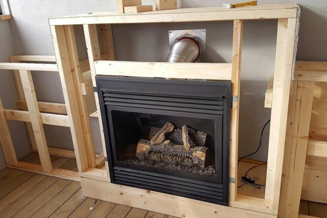 fireplace surrounded by bare frame and venting duct visible