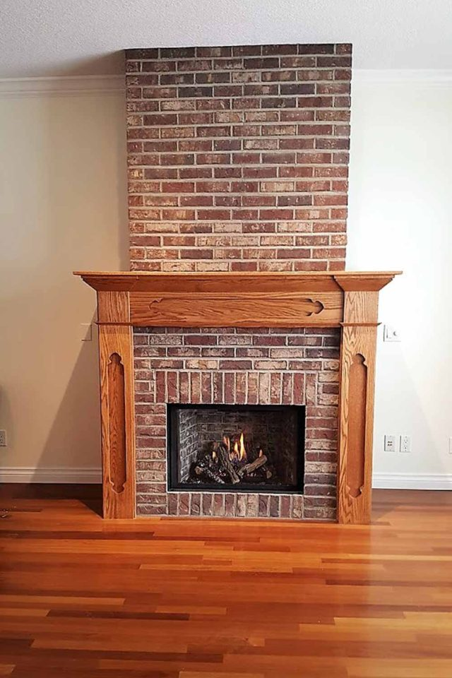 bare brick fireplace with wood paneling