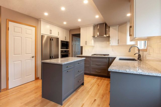 kitchen with double sink, wooden floors and large windows showing gas hob, workstation island, oven and fridge/freezer
